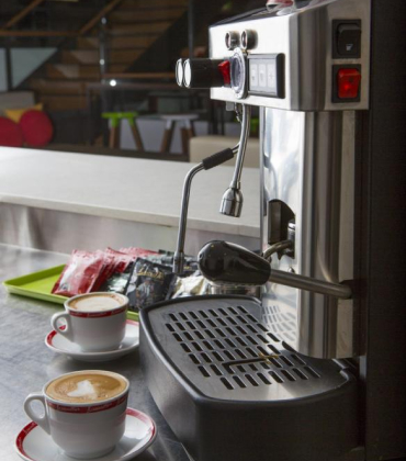 Coffee machine sitting on a table in an office space with two cups of cappuccino next to it